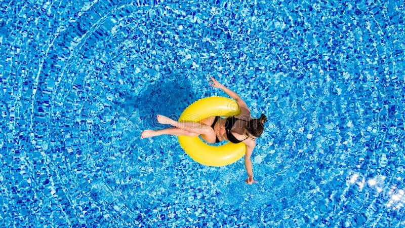 Luchtmening van het jonge donkerbruine vrouw zwemmen op opblaasbare grote geel in de pool Hoogste mening van het slanke dame onts stock foto