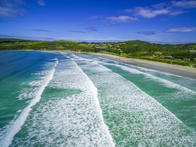 Luchtmening van het verpletteren van oceaangolven en wit zandig strand stock foto's