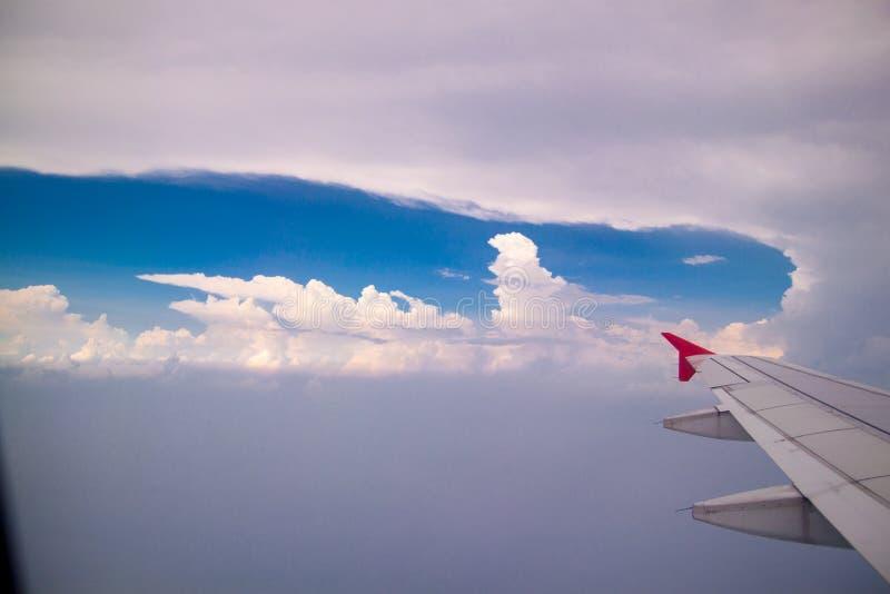 Luchtmening van van het wolken blauwe hemel en vliegtuig vleugelmening door het vliegtuigvenster royalty-vrije stock afbeeldingen
