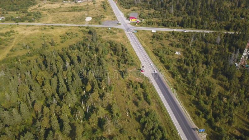 Luchtmening van hierboven van landweg door het groene de zomerbos in de zomer schot Auto het drijven Hoge hoekmening van stock afbeelding