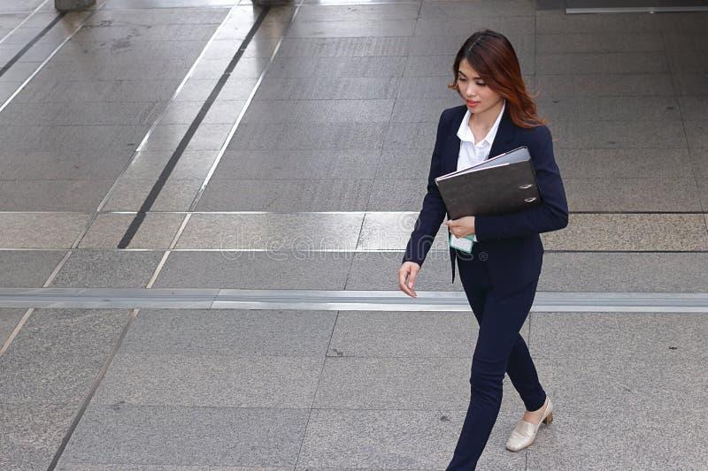 Luchtmening van jonge aantrekkelijke Aziatische het document van de bedrijfsvrouwenholding omslag en het lopen op bevloering in d stock foto