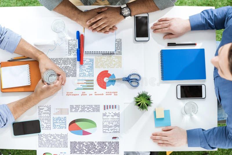 Luchtmening van jonge zakenlieden die bij lijst met documenten zitten en nieuw project bespreken stock afbeeldingen