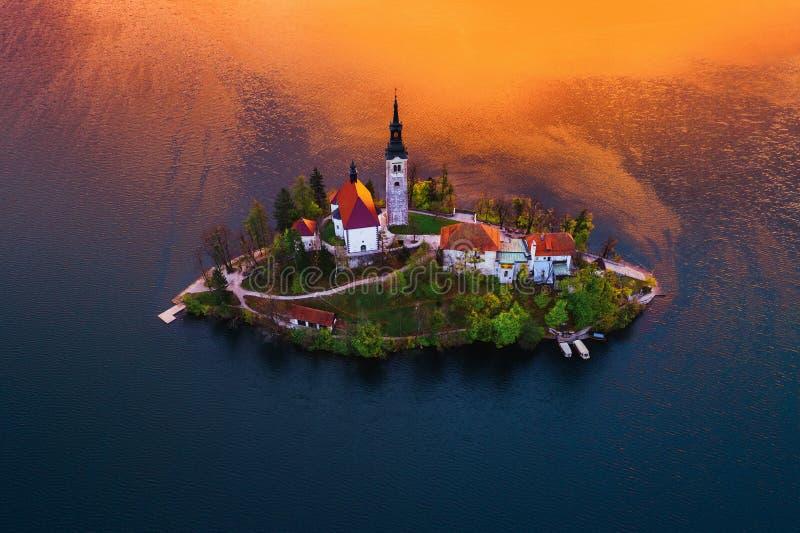Luchtmening van kerk van Veronderstelling in Afgetapt Meer, Slovenië stock foto