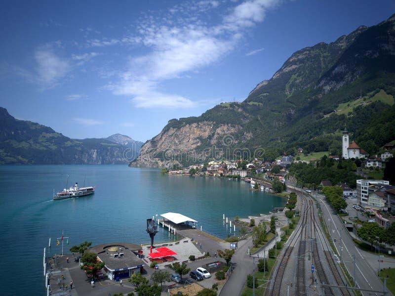 Luchtmening van Meer Luzerne met een sightseeingsboot die op het meer, spoorwegsporen kruisen die zich langs de kust uitrekken stock fotografie