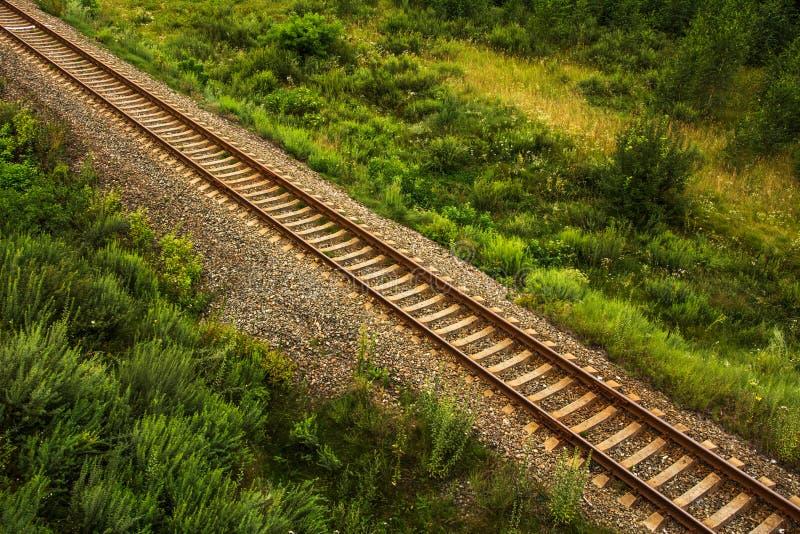 Luchtmening van rechte spoorwegsporen door landbouwgrond stock foto's