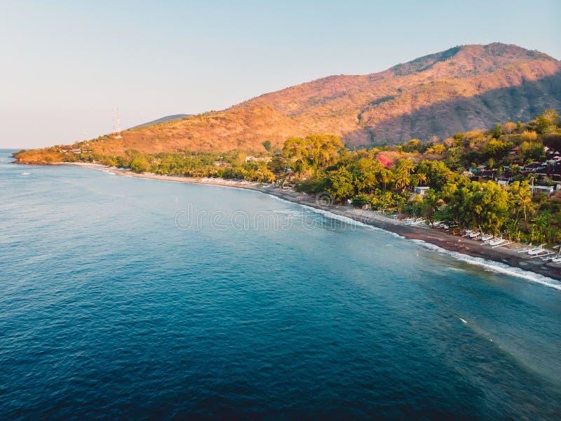 Luchtmening van strand met blauw oceaan en warm zonsonderganglicht in Amed, Bali stock afbeeldingen