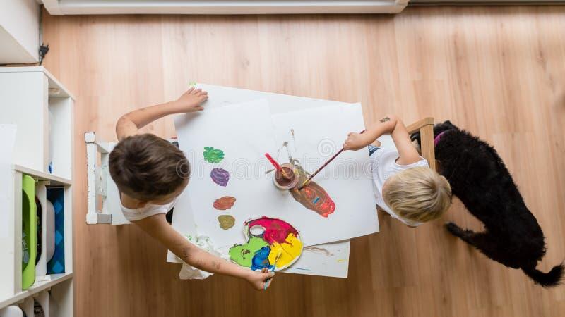 Luchtmening van twee peuterkinderen die met waterkleur schilderen stock foto