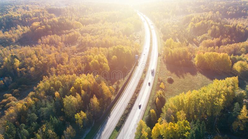 Luchtmening van weg in de herfstbos bij zonsondergang Verbazend landschap met landelijke weg, bomen met rode en oranje bladeren royalty-vrije stock afbeeldingen