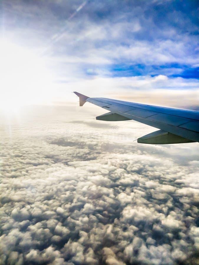 Luchtmening van zachte wolken en vliegtuigvleugel op zonsopgang door een vliegtuigenvenster royalty-vrije stock fotografie