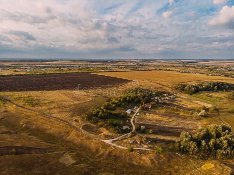 Luchtmenings landelijk landschap, klein dorp met huizen onder landbouwgebieden en weiden stock fotografie