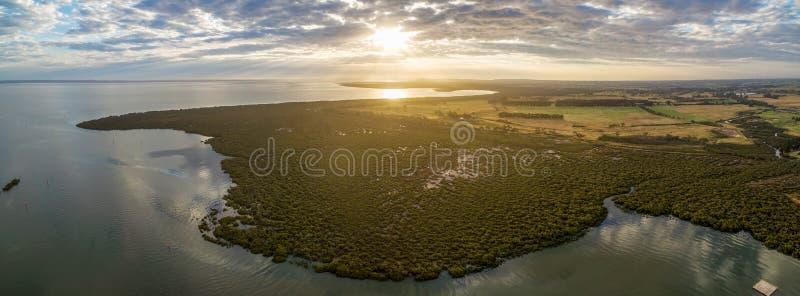 Luchtpanorama van mangroven en landbouwgebieden dichtbij oceaankustlijn bij mooie zonsondergang royalty-vrije stock fotografie
