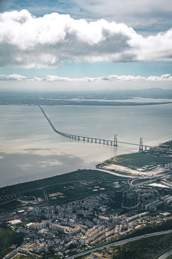 Luchtpanoramamening over 25 DE Abril Bridge De brug verbindt de stad van Lissabon met de gemeente van royalty-vrije stock foto