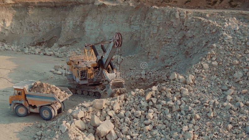 Luchtschot die Zware Stortplaatsvrachtwagen laden bij de Bovengrondse Mijnbouwplaats stock afbeelding