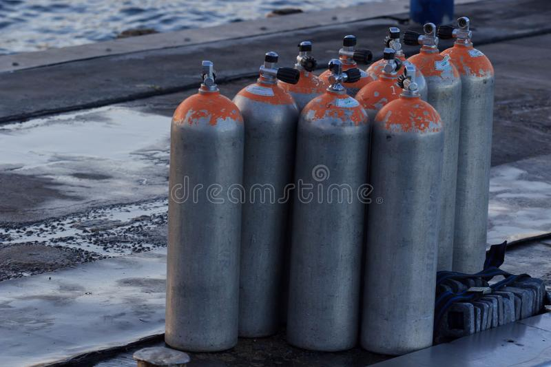 Luchttanks voor Vrij duiken in een houten platform dichtbij het het duiken witte het zandstrand van de clubmaldiven Mooie Zonsond stock foto