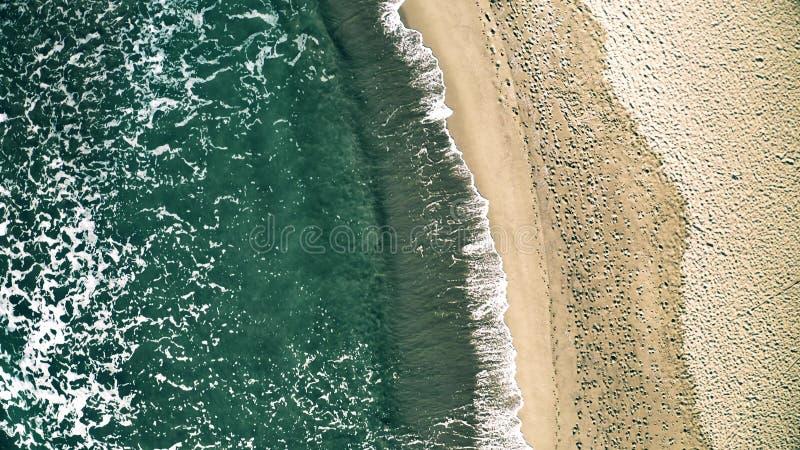 Luchttop down mening van overzeese branding op het strand met vele voetafdrukken stock afbeelding