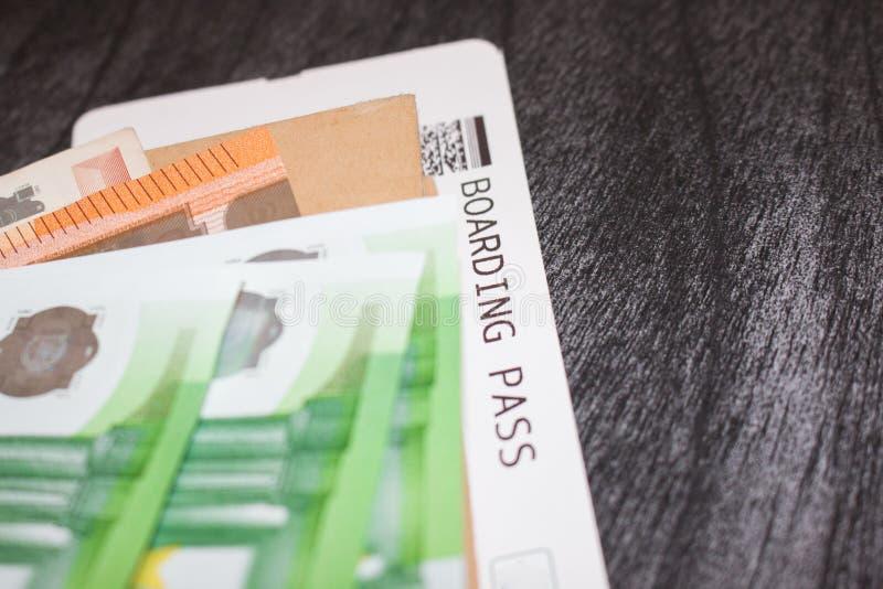 Luchtvaartlijnkaartjes en geld op de lijst Euro bankbiljetten en instapkaart Het concept het kopen van het kaartje voor reis Grey royalty-vrije stock afbeeldingen