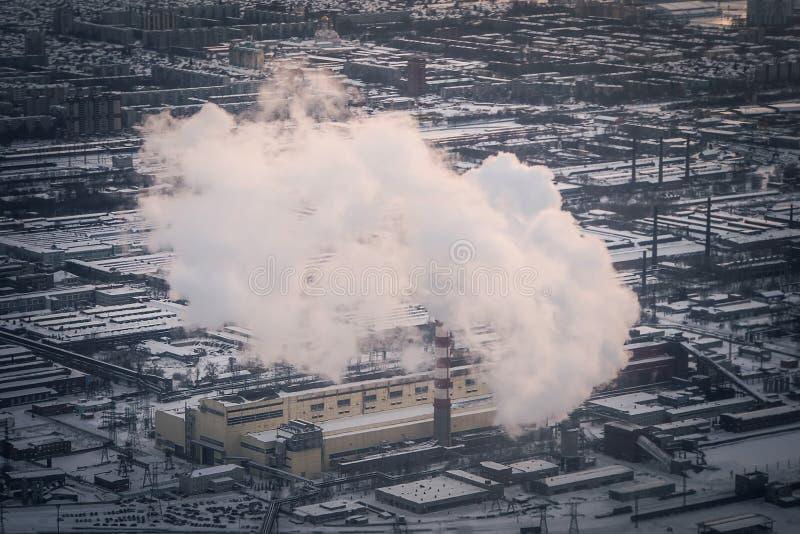 Luchtvervuiling door rook die uit twee fabrieksschoorstenen komt stock foto's