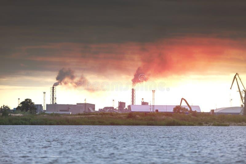 Luchtvervuiling door rook die uit twee fabrieksschoorstenen komt Industriezone in de stad stock afbeeldingen