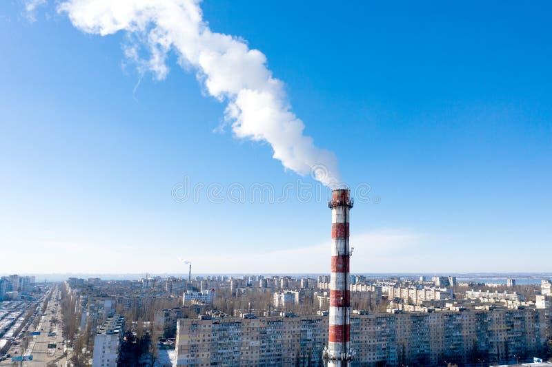 Luchtvervuiling, fabriekspijpen, rook door schoorstenen op hemelachtergrond Concept de industrie, ecologie, stoominstallatie, het royalty-vrije stock afbeeldingen