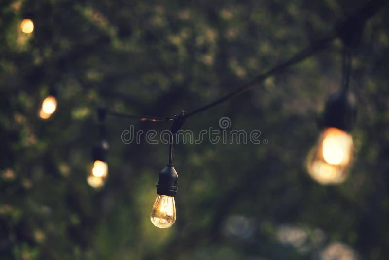 Luci all'aperto della corda che appendono su una linea fotografie stock libere da diritti