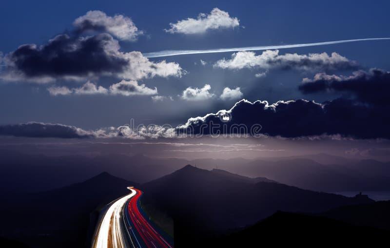 Luci dell'automobile sulla strada alla notte immagine stock libera da diritti