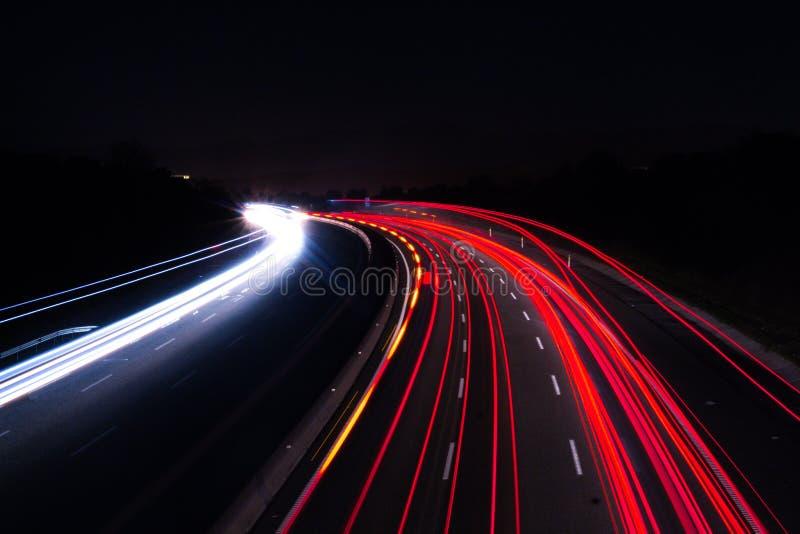 Luci dell'automobile sulla strada principale con una notte scura fotografie stock libere da diritti