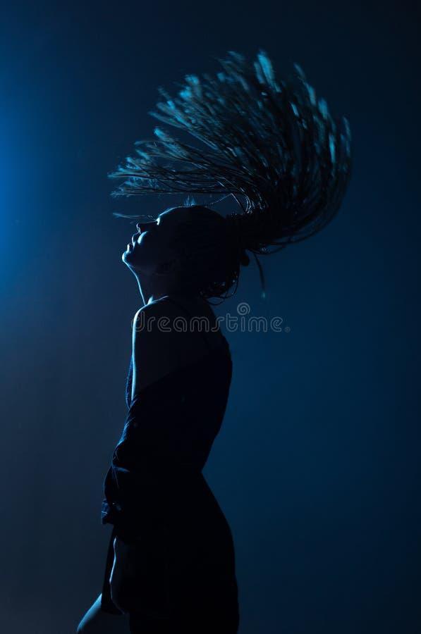 Luci della pista da ballo dell'impermeabile delle trecce di afro della donna immagine stock
