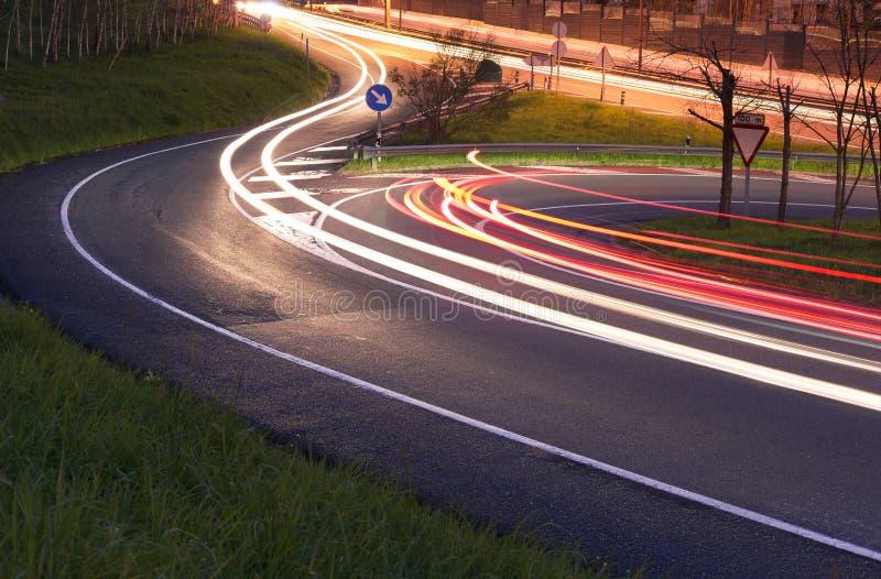 Luci delle automobili nella strada alla notte immagine stock