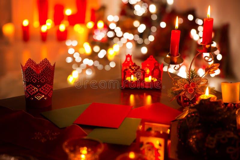 Luci delle candele natalizie, lettera di Natale sul tavolo, illuminazione notturna disfocata fotografia stock libera da diritti