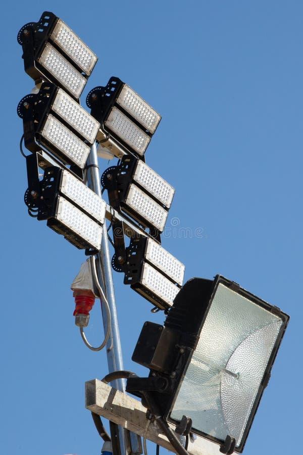 Luci dello stadio dei proiettori dell'arena di sport contro il fondo blu del cielo di giorno fotografia stock libera da diritti