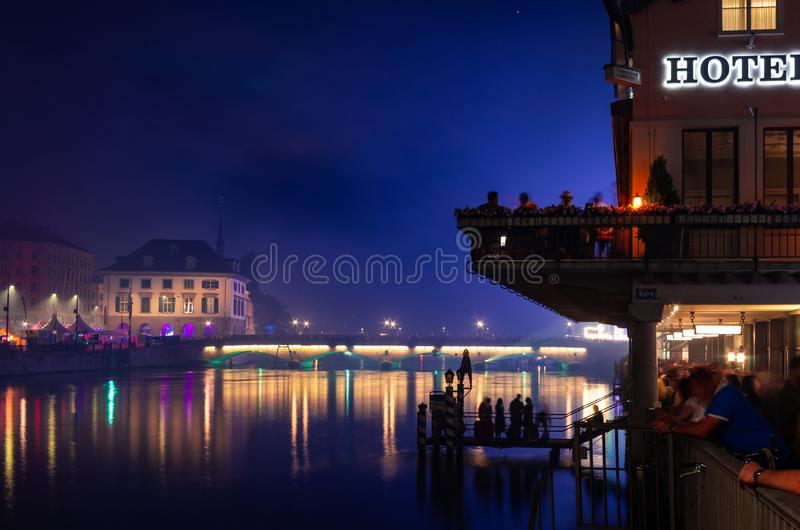 Luci di lunghezza della città di esposizione di ora blu della città di Zurigo riflesse in fiume, in vecchia costruzione ed in fol fotografia stock libera da diritti