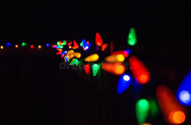 Luci di Natale alla notte lungo un recinto fotografie stock