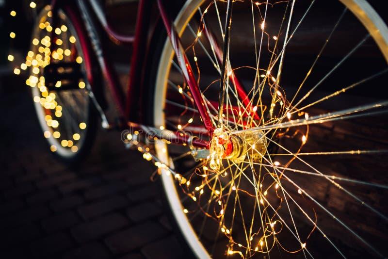 Luci di Natale su struttura del fondo della bici in citt? immagini stock