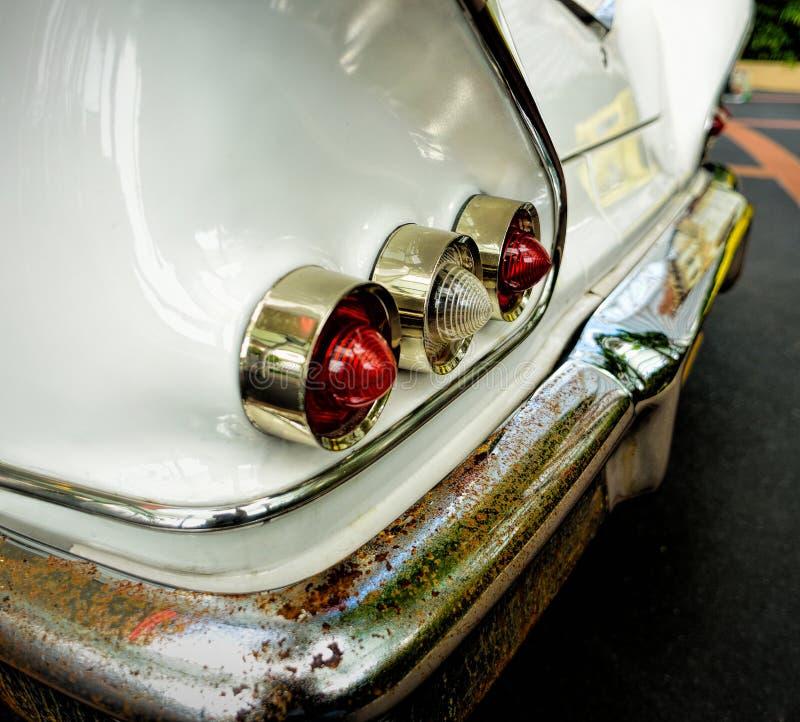 Luci posteriori dell'automobile classica con il paraurti arrugginito fotografia stock