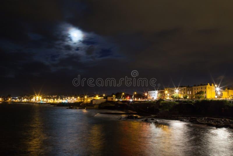 Luci rocciose della costa e della città di mare di notte immagini stock libere da diritti
