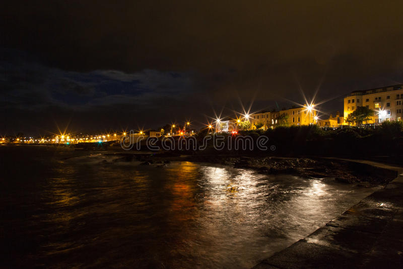 Luci rocciose della costa e della città di mare di notte fotografia stock libera da diritti