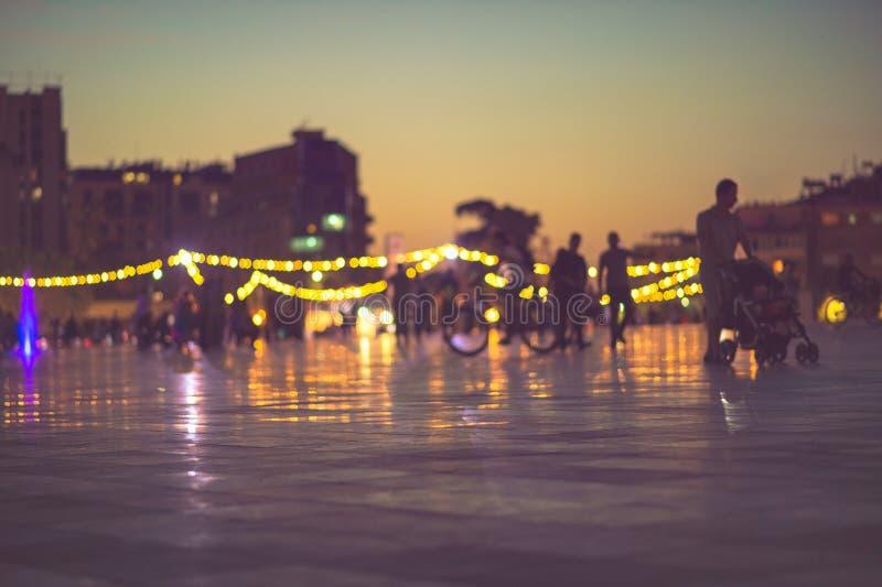 Luci sfuocatura, tramonto e pedone di sera di vita di città fotografia stock libera da diritti