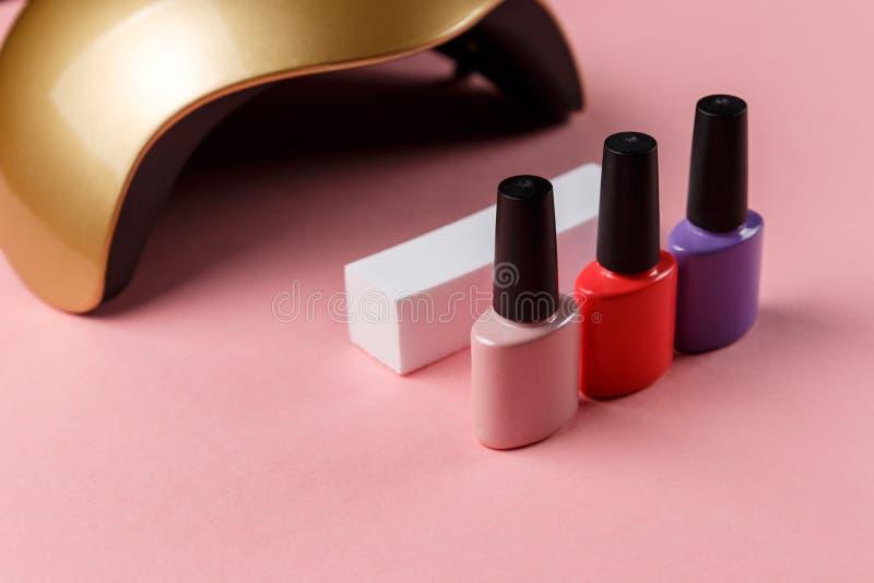 Luci UV della lampada per i chiodi e l'insieme del cosmetico immagini stock libere da diritti