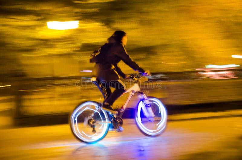 Luci vaghe della città e di una siluetta di un ciclista con gl fotografia stock