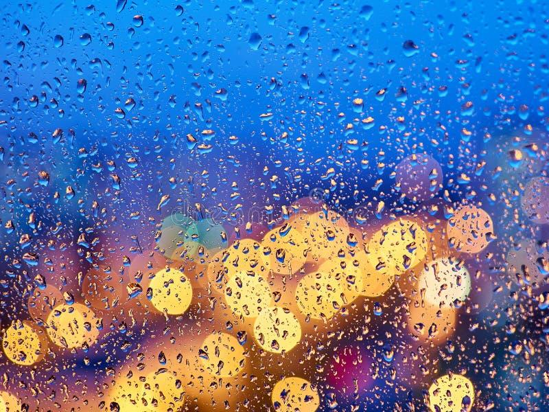 Luci variopinte della città di notte attraverso il vetro bagnato immagine stock