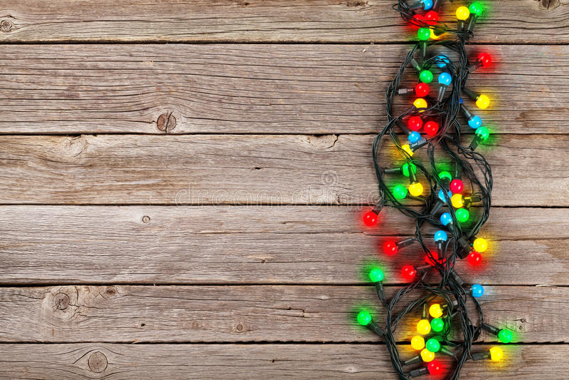 Luci variopinte di Natale sopra fondo di legno immagine stock