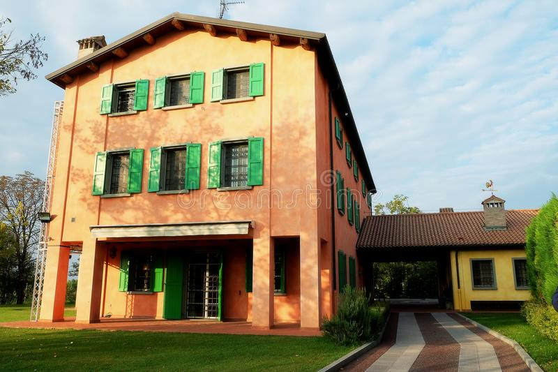 Luciano Pavarotti house in Modena, Italy. The orange house with green windows of Luciano Pavarotti house in Modena, Italy stock photo