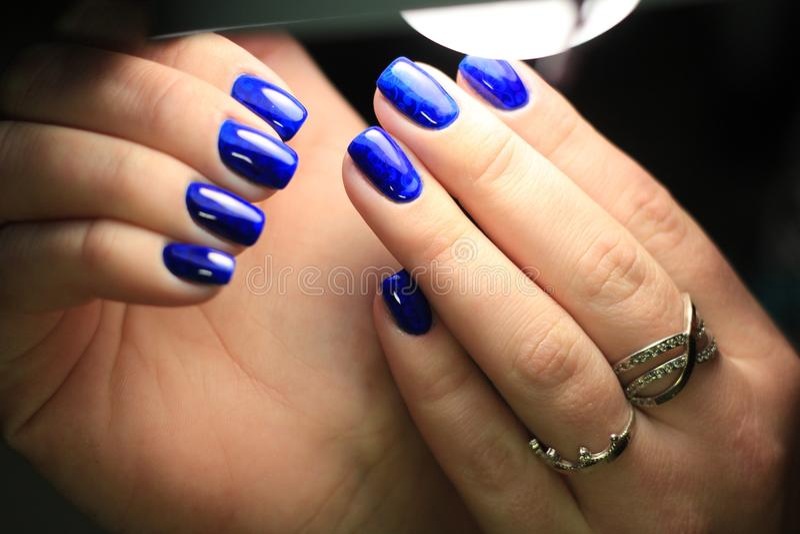 Lucidatura blu del gel del vetro macchiato del manicure con un'immagine fotografia stock libera da diritti