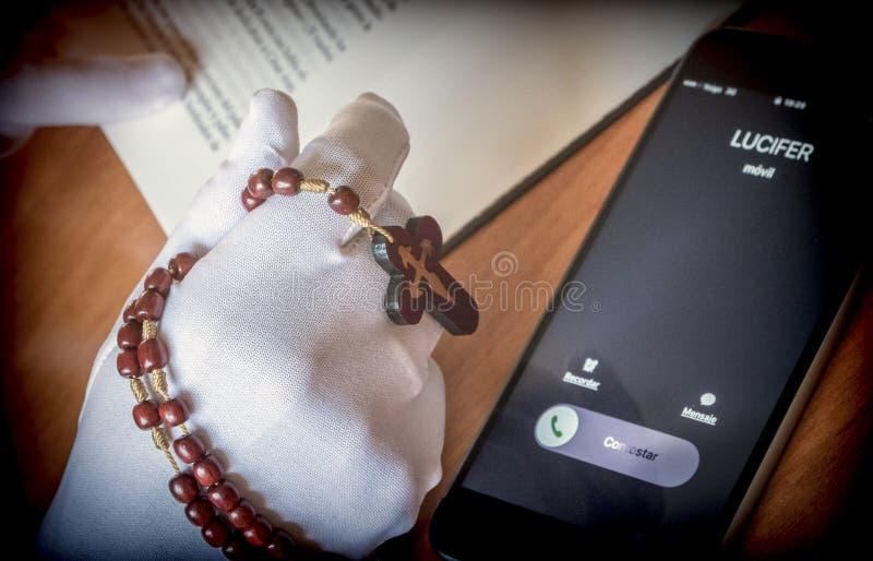 Lucifer dzwoni kobiety modlenie z różanem, zdjęcia stock
