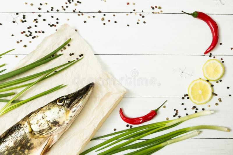 Lucio fresco con las especias en una tabla de madera blanca Alimento dietético, pescado del río imagenes de archivo