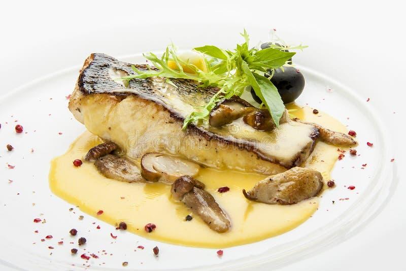 Lucioperca con i funghi e le patate di porcini Su un piatto bianco fotografia stock libera da diritti