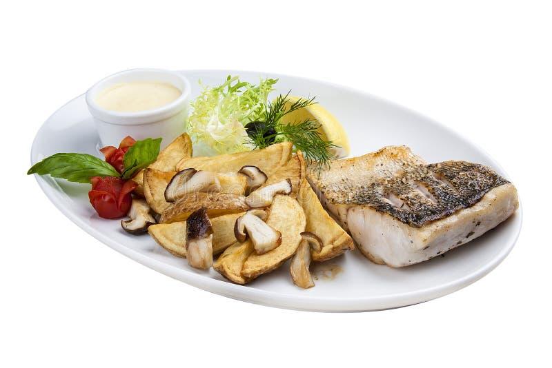 Lucioperca con i funghi e le patate di porcini Su un piatto bianco immagini stock libere da diritti