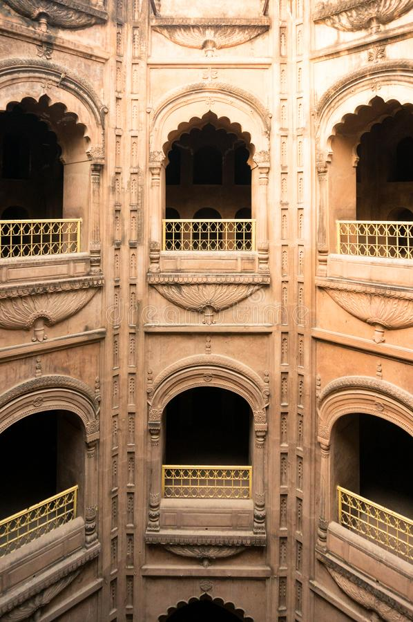 The arched windows at the bouli in bara imambara. Lucknow, India - 3rd feb 2018: The arched sandstone windows of mughal architecture. Shot at the bata imambara royalty free stock photo