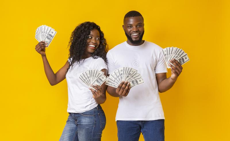 Lucky african young man and woman holding dollars royalty free stock images