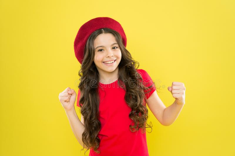 Lucky and beautiful. Kid girl long healthy shiny hair wear red hat. Little girl with long hair. Kid happy cute face. Adorable curly hair yellow background stock photos